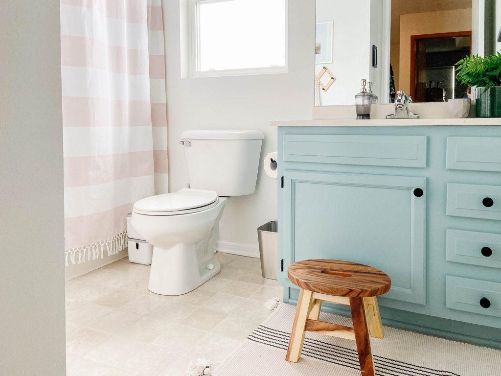 Photo de la salle de bains avec lavabo bleu et tabouret en bois