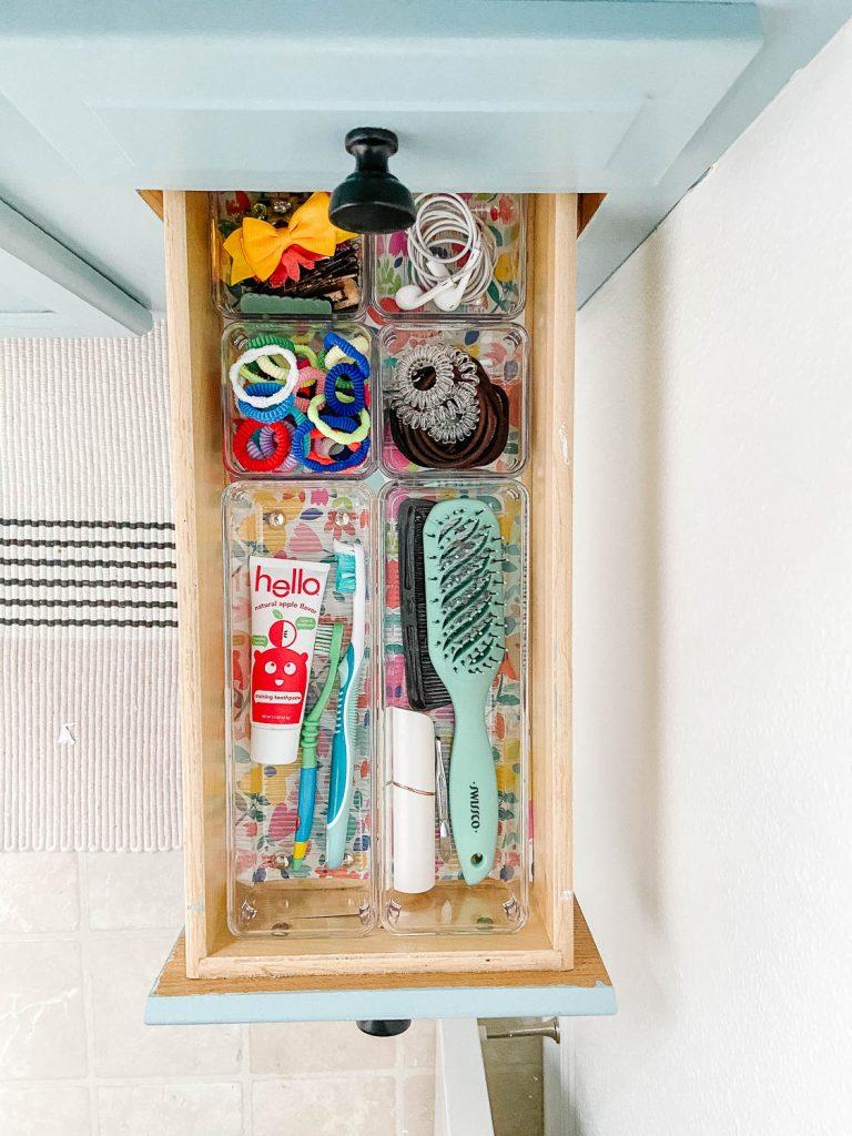 Tiroir de salle de bains avec produits de soins capillaires dans des récipients transparents