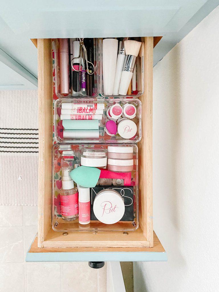 Tiroir de la salle de bain avec des récipients transparents remplis de maquillage