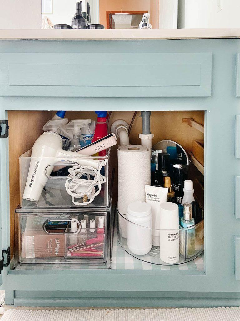 Armoire de salle de bains avec produits pour cheveux et produits de nettoyage