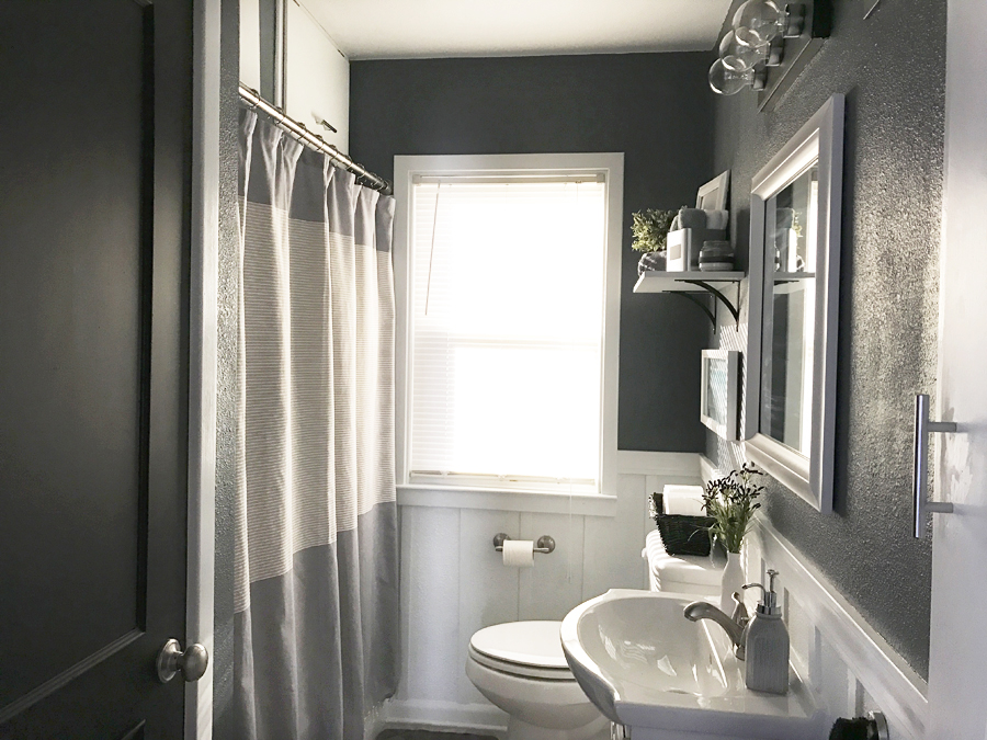 Regardez cette salle de bains gris neutre avec des boiseries blanches. J'adore cette pièce du One Room Challenge que j'ai remodelée ! C'est incroyable ce qu'on peut faire avec une petite salle de bain.